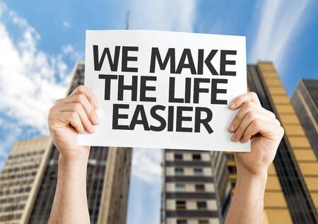 easier: Hands holding We Make the Life Easier card with city background