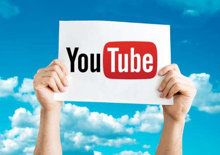 Hände halten YouTube-Karte mit Himmel im Hintergrund