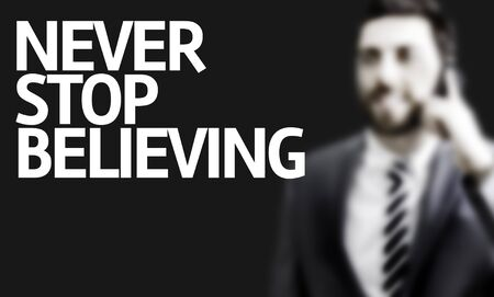 believing: Business man with the text Never Stop Believing in a concept image Stock Photo