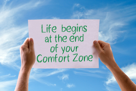 begins: Hands holding Life Begins At The End Of Your Comfort Zone card with sky background