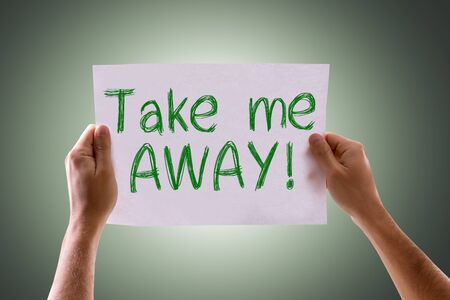 free me: Hands holding cardboard with Take Me Away on green background Stock Photo