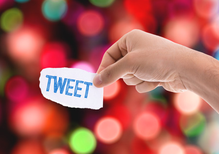 tweet: Hand holding piece of paper with Tweet on blue background Stock Photo