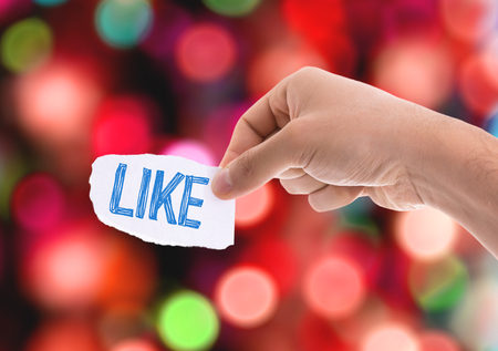 approval rate: Hand holding piece of paper with Like on sky background Stock Photo