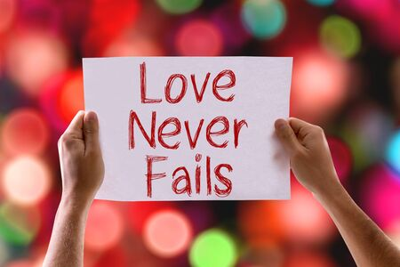 fails: Hands holding cardboard with Love Never Fails on bokeh background