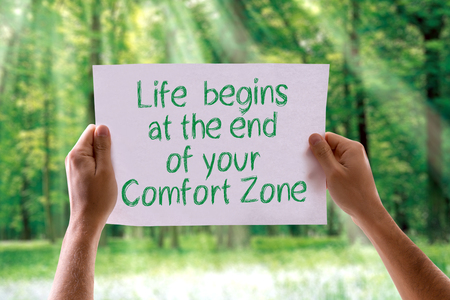 begins: Hands holding Life Begins At The End Of Your Comfort Zone card with nature background