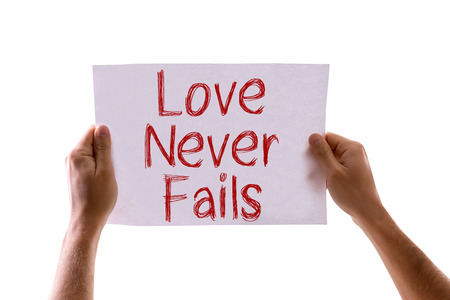 fails: Hands holding cardboard with Love Never Fails isolated on white background