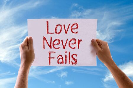 fails: Hands holding cardboard with Love Never Fails on sky background Stock Photo