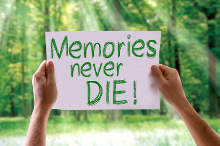 Hands holding Memories Never Die card with nature background Stock Photo