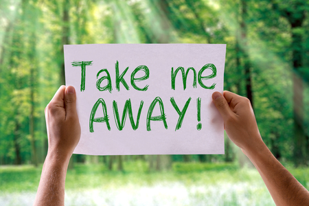 Hands holding cardboard with Take Me Away on nature background Stock Photo