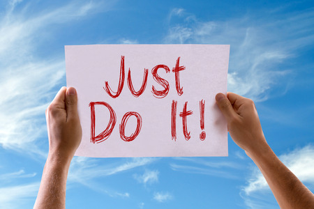 Hands holding Just Do It card with sky background