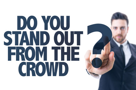 adentro y afuera: hombre de negocios que señala el texto: ¿Usted se coloca fuera de la muchedumbre? Foto de archivo