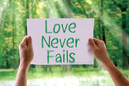 fails: Hands holding cardboard with Love Never Fails on nature background