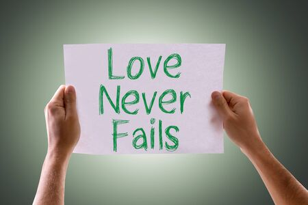 fails: Hands holding cardboard with Love Never Fails on green background Stock Photo