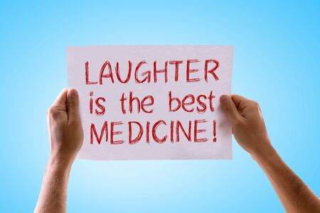 longevity drugs: Hands holding cardboard with Laughter is the Best Medicine on sky background Stock Photo