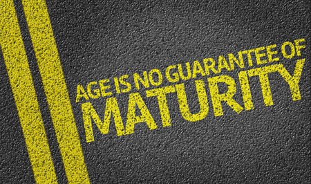 maturity: Age is No Guarantee Of Maturity written on the road Stock Photo