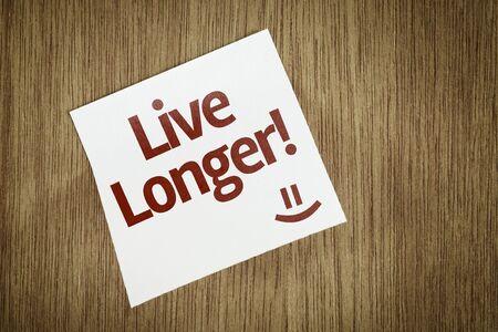 longer: Live Longer written on paper note on wood texture background Stock Photo