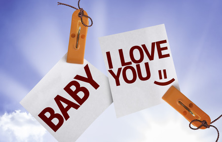 nota: Baby, I Love You written on paper note with clips on sky background