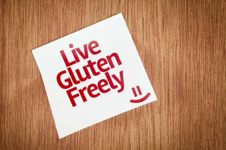 freely: Live Gluten Freely written on paper note on wood texture background