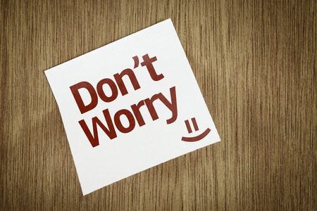 dont worry: Dont Worry written on paper note on wood texture background