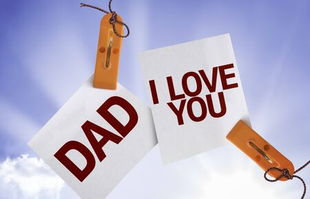 paternal: Dad I Love You written on paper note with clips on sky background