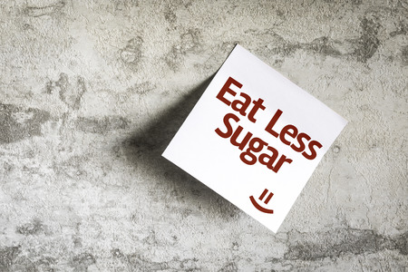Eat Less Sugar written on paper note on texture background Stock Photo