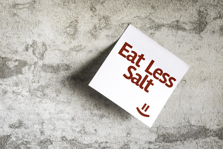 Eat Less Salt written on paper note on texture background