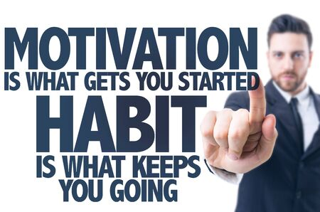 Business man pointing the text Motivation is What Gets you Started Habit Is What Keeps You Going
