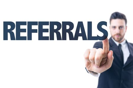 referidos: Business man pointing to transparent board with text: Referrals Foto de archivo