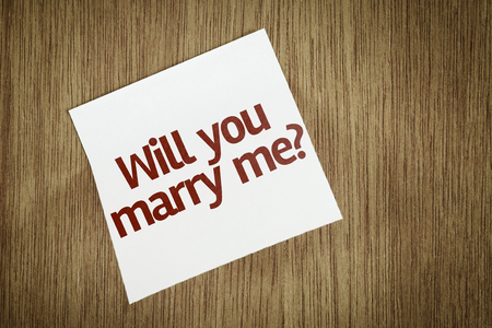 will you marry me: Will you Marry Me? written on sticky note on wooden background