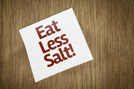 reduce: Eat Less Salt written on sticky note on wooden background