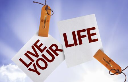 Live Your Life on paper notes with sky background Stock Photo