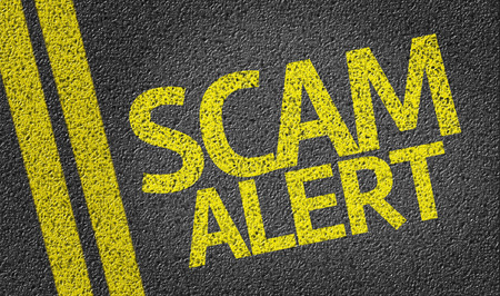 scamming: Scam Alert written on road Stock Photo