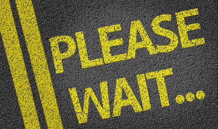 Please Wait written on the road