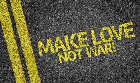 hacer el amor: Haz el amor y no la guerra escrito en la carretera de asfalto