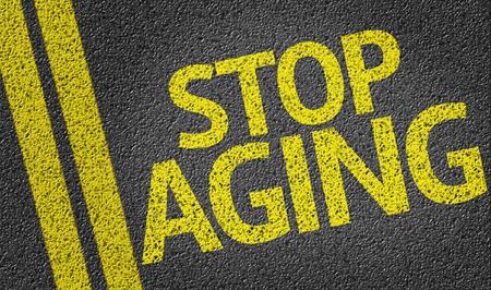 aging: Stop Aging written on asphalt road Stock Photo