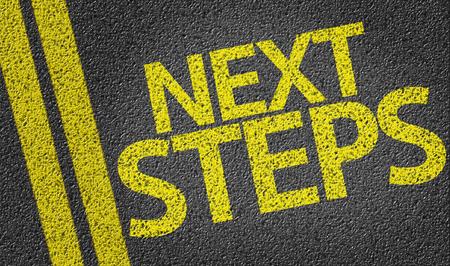 Next Steps written on asphalt road
