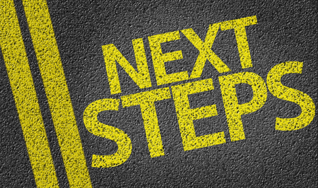 Next Steps written on asphalt road