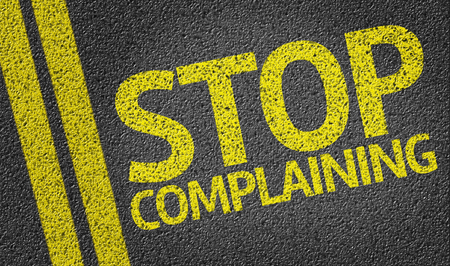 Stop Complaining written on asphalt road Stock Photo