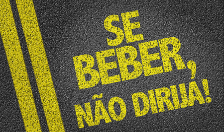 drink responsibly: If You Drink Do Not Drive in Portuguese written on asphalt road