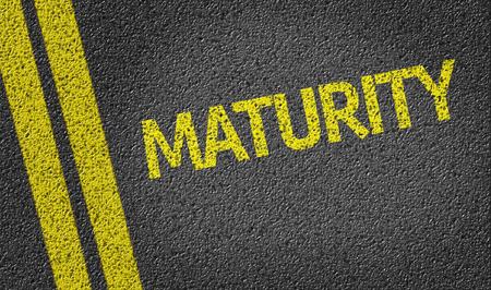 maturity: Maturity written on asphalt road Stock Photo