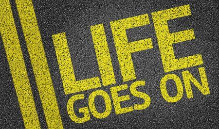 Life Goes On written on asphalt road