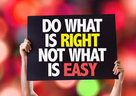 Hands holding card with text Do what is right not what is easy on bokeh background