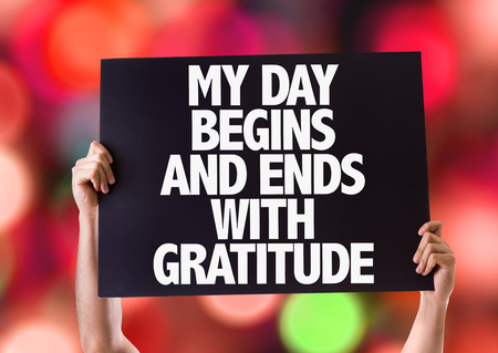 begins: Hands holding blackboard with My Day Begins And Ends With Gratitude on bokeh background