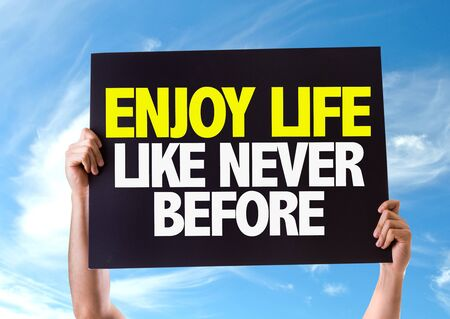 enjoy life: Hands holding blackboard with Enjoy Life Like Never Before on sky background