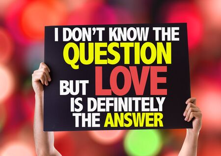 Hands holding blackboard with I Dont Know The Question But Love Is Definitely The Answer on bokeh background Stock Photo