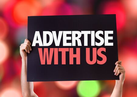 advertise with us: Hands holding blackboard with Advertise With Us on bokeh background Stock Photo
