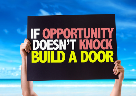 knock on door: Hands holding card with text If opportunity doesnt knock build a door on sky background Stock Photo