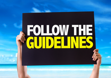 Hands holding blackboard with Follow The Guidelines on beach background
