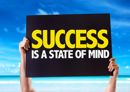 Hands holding blackboard with Success Is A State Of Mind on beach background Stock Photo
