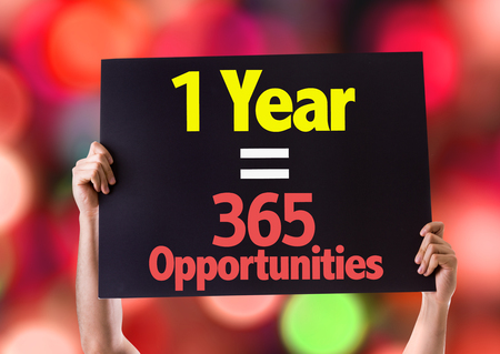 one year: Hands holding blackboard with One Year Equals 365 Opportunities on bokeh background